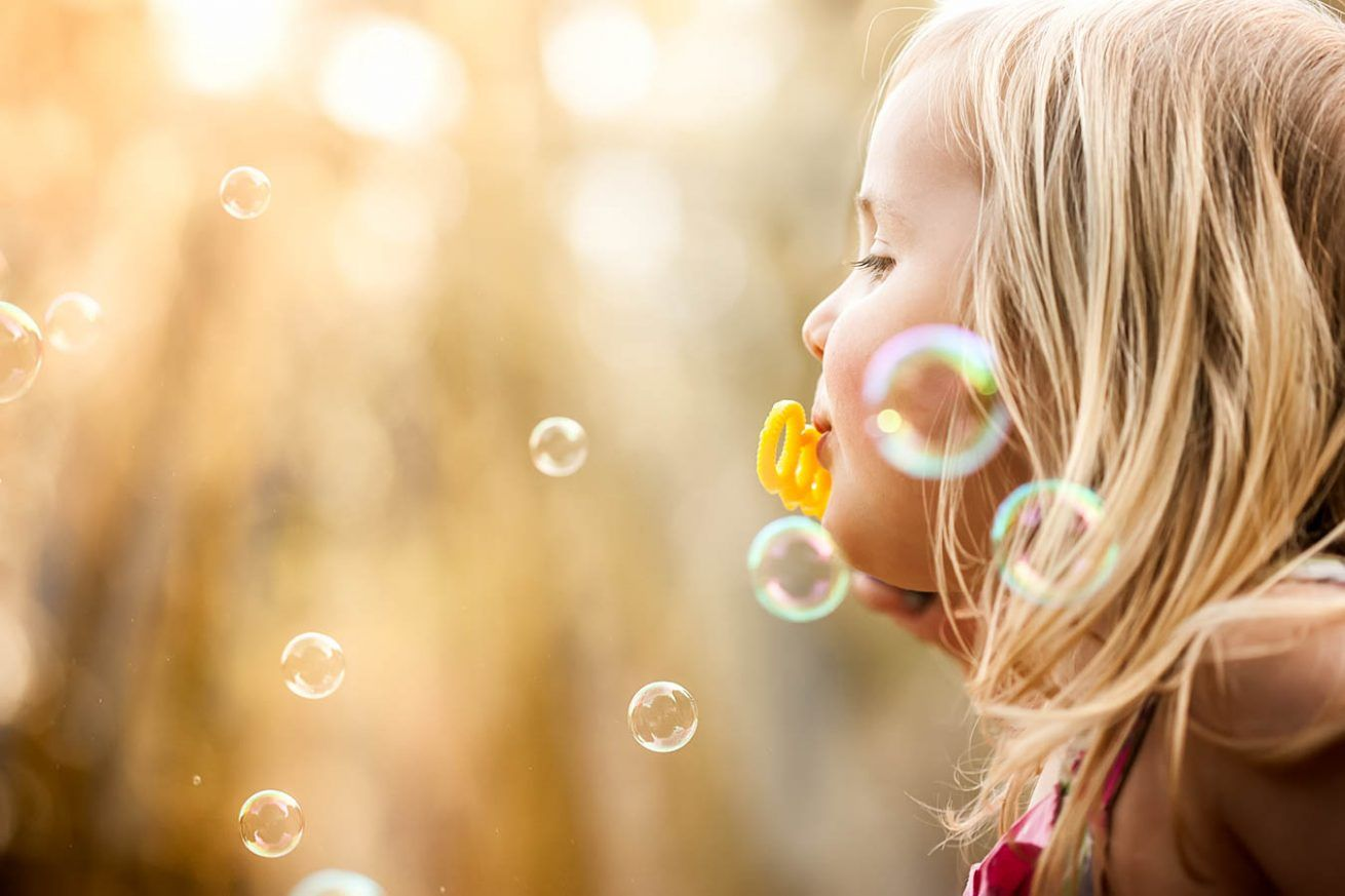 A child blows bubbles in the golden sunlight.
